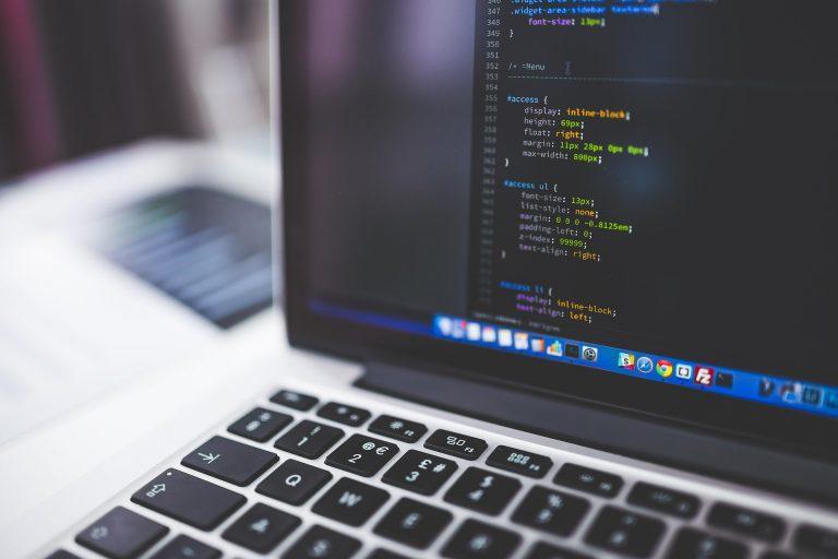 Imagem mostra um notebook com códigos de programação na tela.