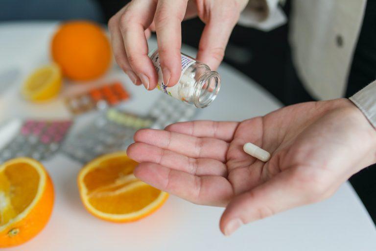 Mão de pessoa com cápsula de suplemento e laranjas na mesa.