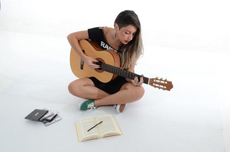 Image shows a woman playing the guitar along with a book.