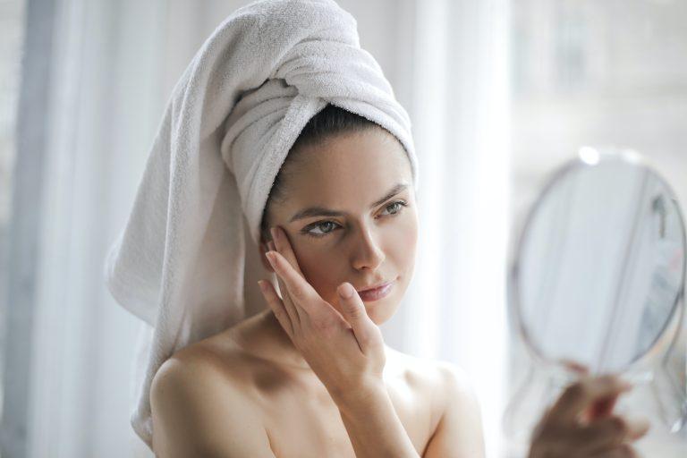 Mulher tratando da pele no espelho.