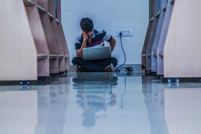 Imagem mostra um jovem concentrado olhando para um notebook.