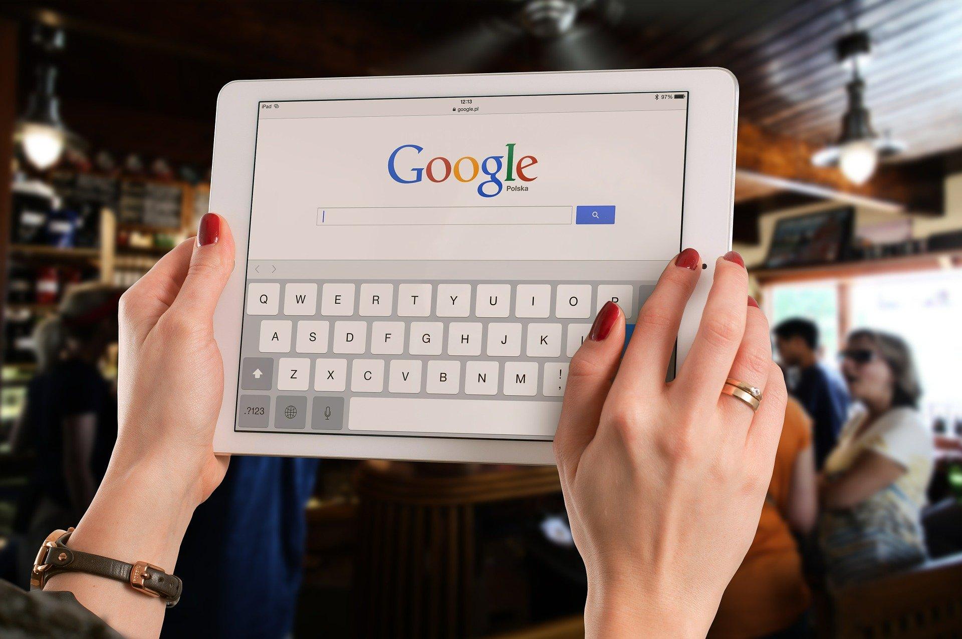 Imagem mostra uma pessoa segurando um tablet com o Google em destaque.