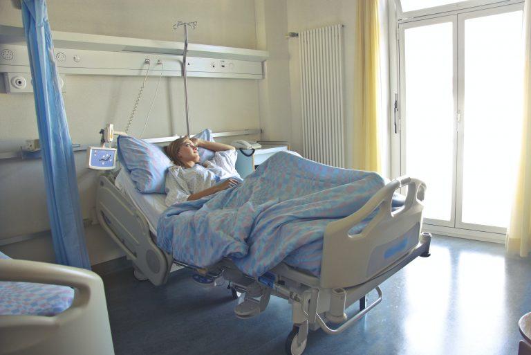 Mulher deitada em cama no hospital.