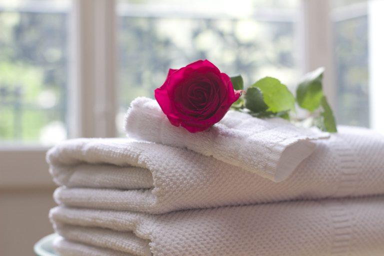 Toalhas de banho branca com botão de rosa.