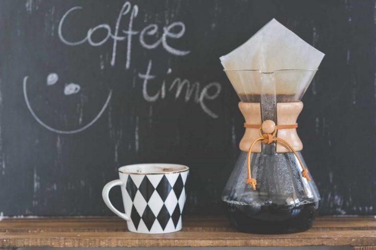 Jarra de café, com coador e filtro de papel e xícara ao lado.