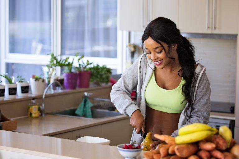 Imagem de uma mulher cortando frutas.
