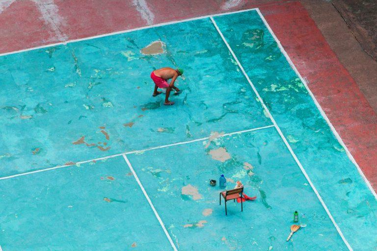 Homem pintando quadra de esporte.