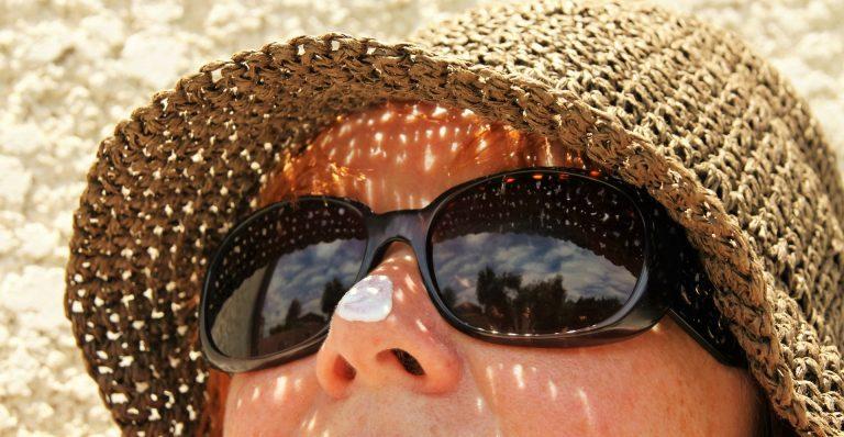 Mulher com protetor solar na ponta do nariz, com óculos escuros e chapéu de palha.