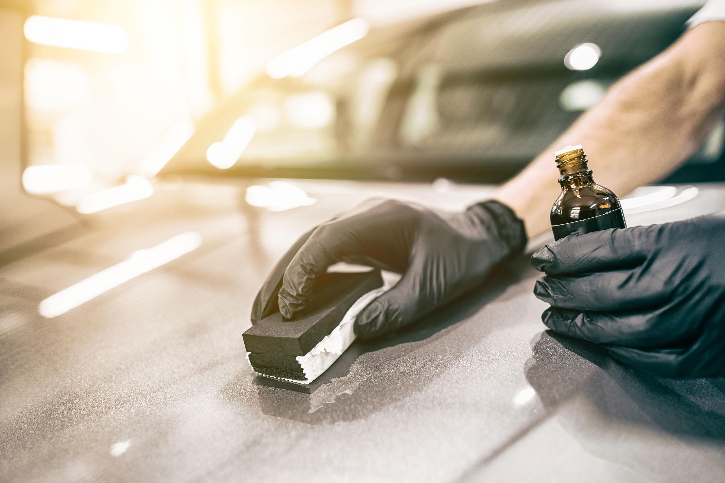 Imagem mostra uma pessoa passando cera em um automóvel.