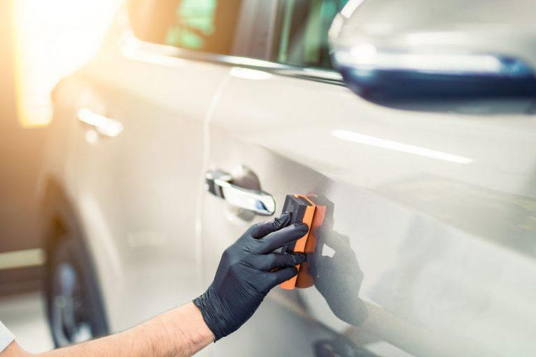 Imagem mostra uma pessoa espalhando cera em um carro