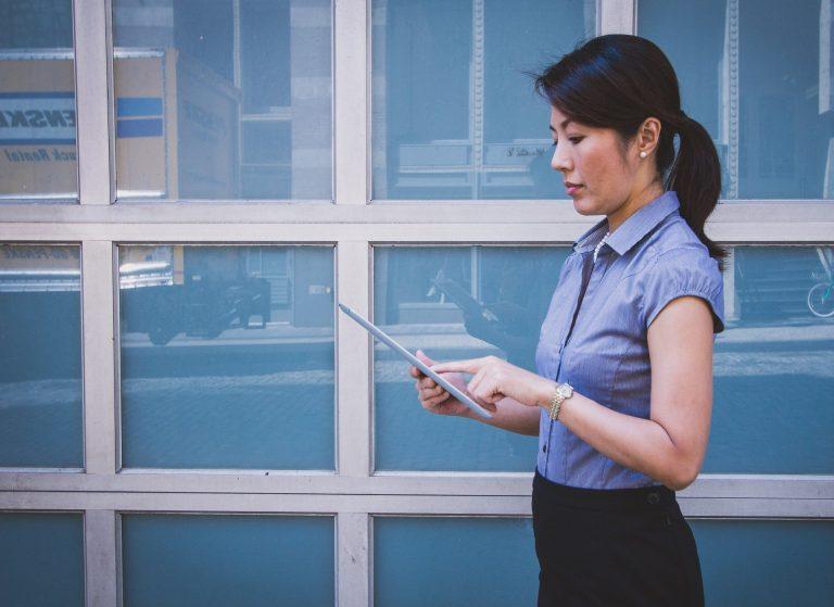 Imagem mostra uma mulher vestindo roupa social e usando um tablet.