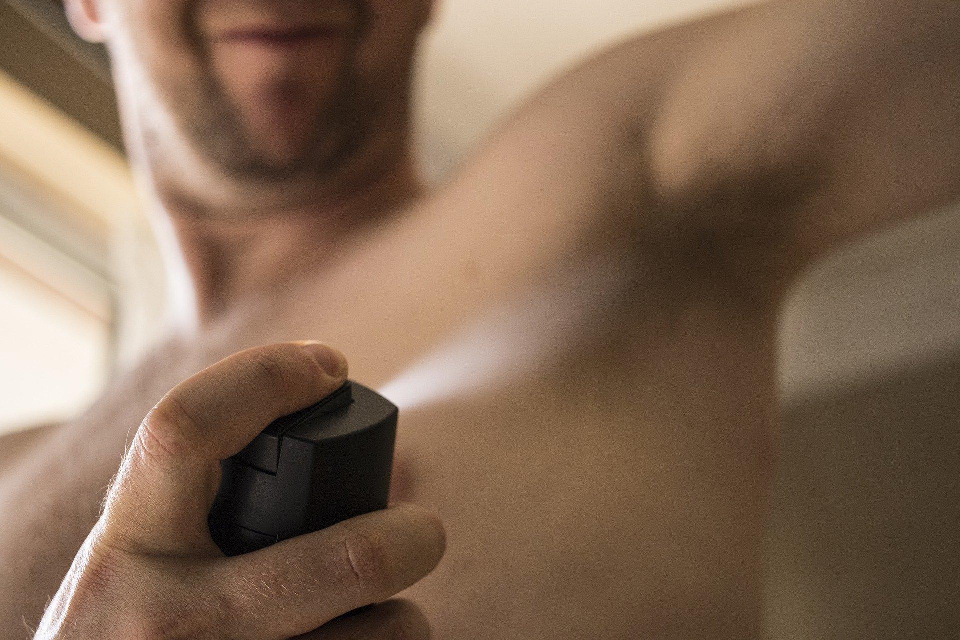 Imagem mostra um homem passando desodorante.
