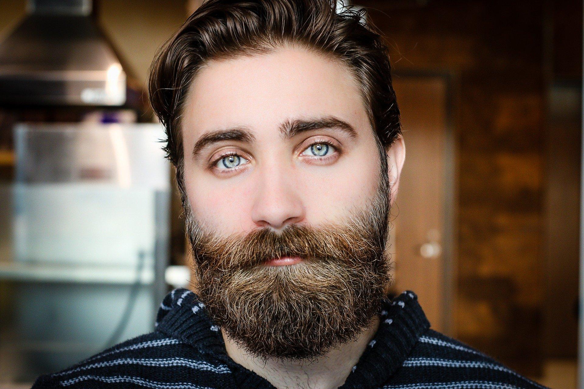Imagem mostra um homem barbudo em destaque.