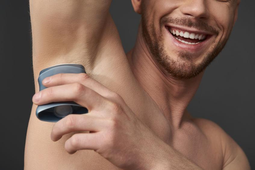 Imagem mostra um homem passando um desodorante do tipo roll-on.