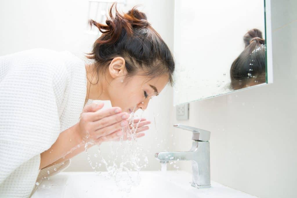 Mulher lavando o rosto.