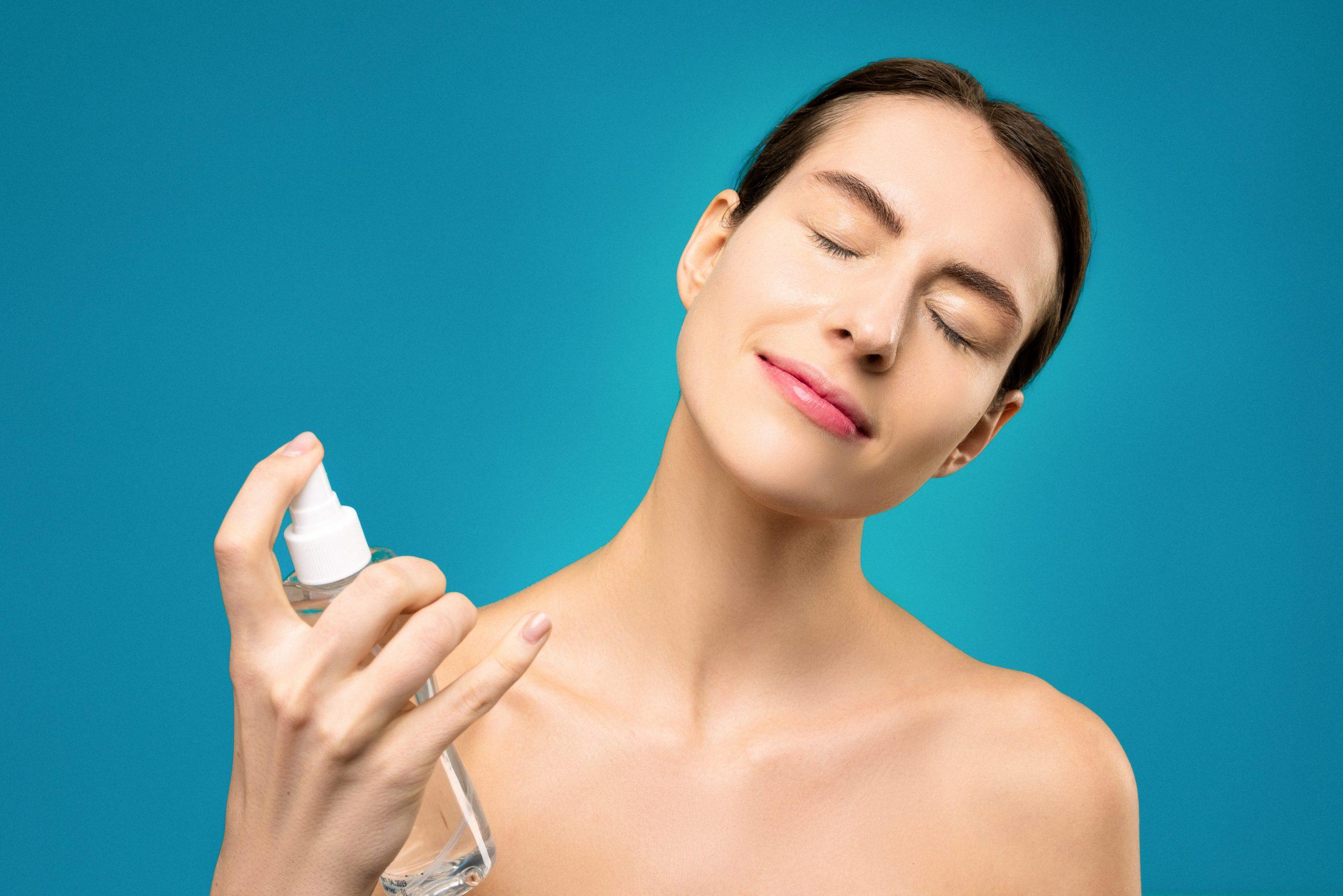 Imagem de uma mulher aplicando um cosmético no rosto.