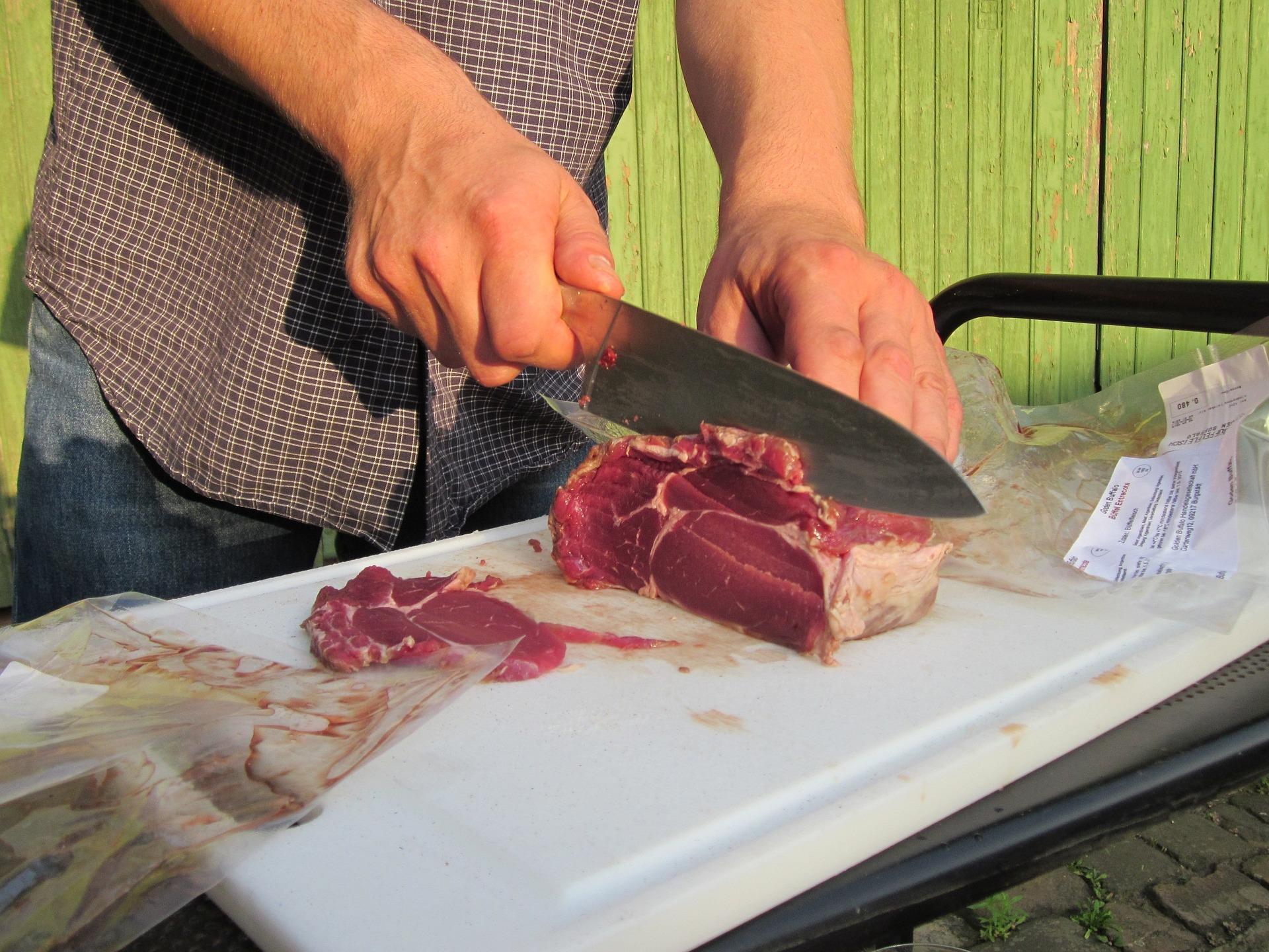 Imagem mostra um homem usando uma faca para cortar um pedaço de carne.