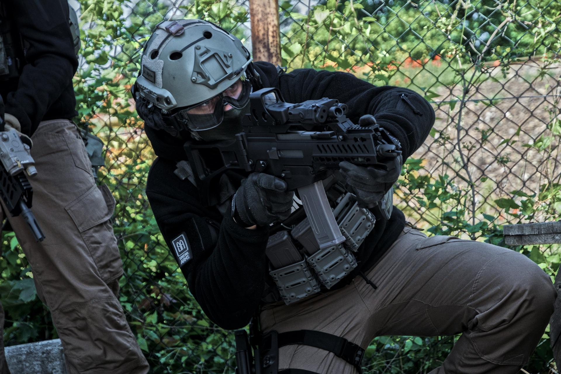 Imagem mostra um homem praticando airsoft com uma máscara de proteção.