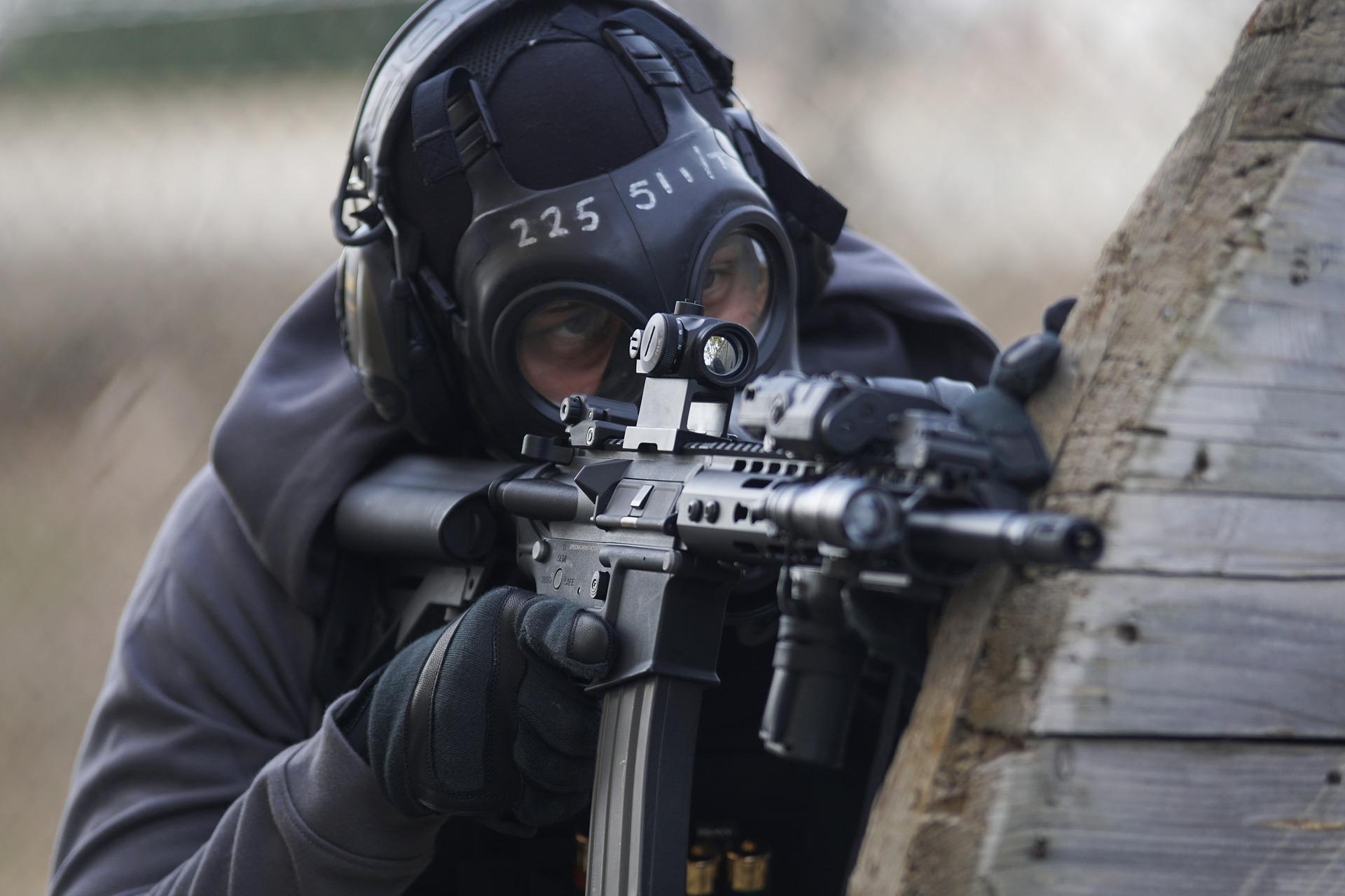 Imagem mostra uma pessoa praticando airsoft usando uma máscara de proteção.