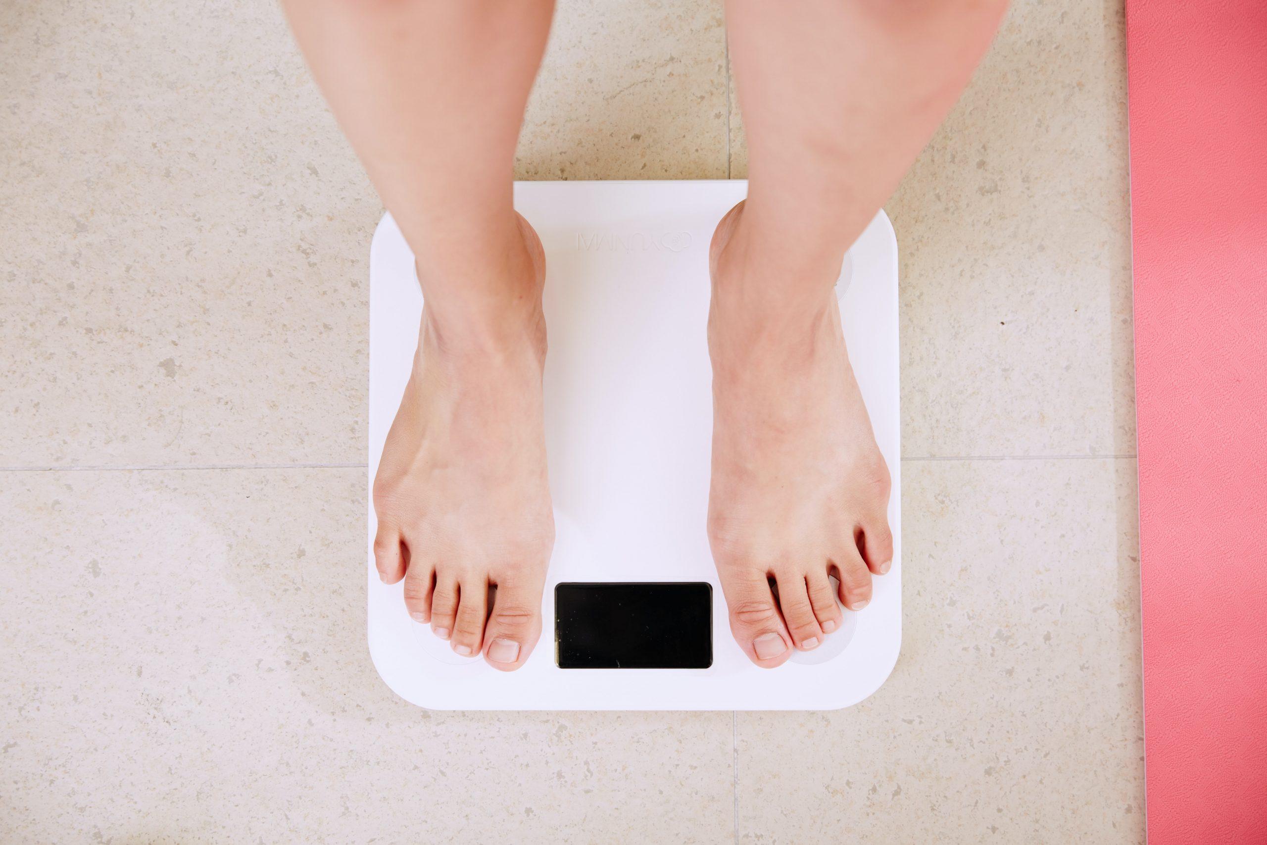 Imagem de uma mulher se pesando.