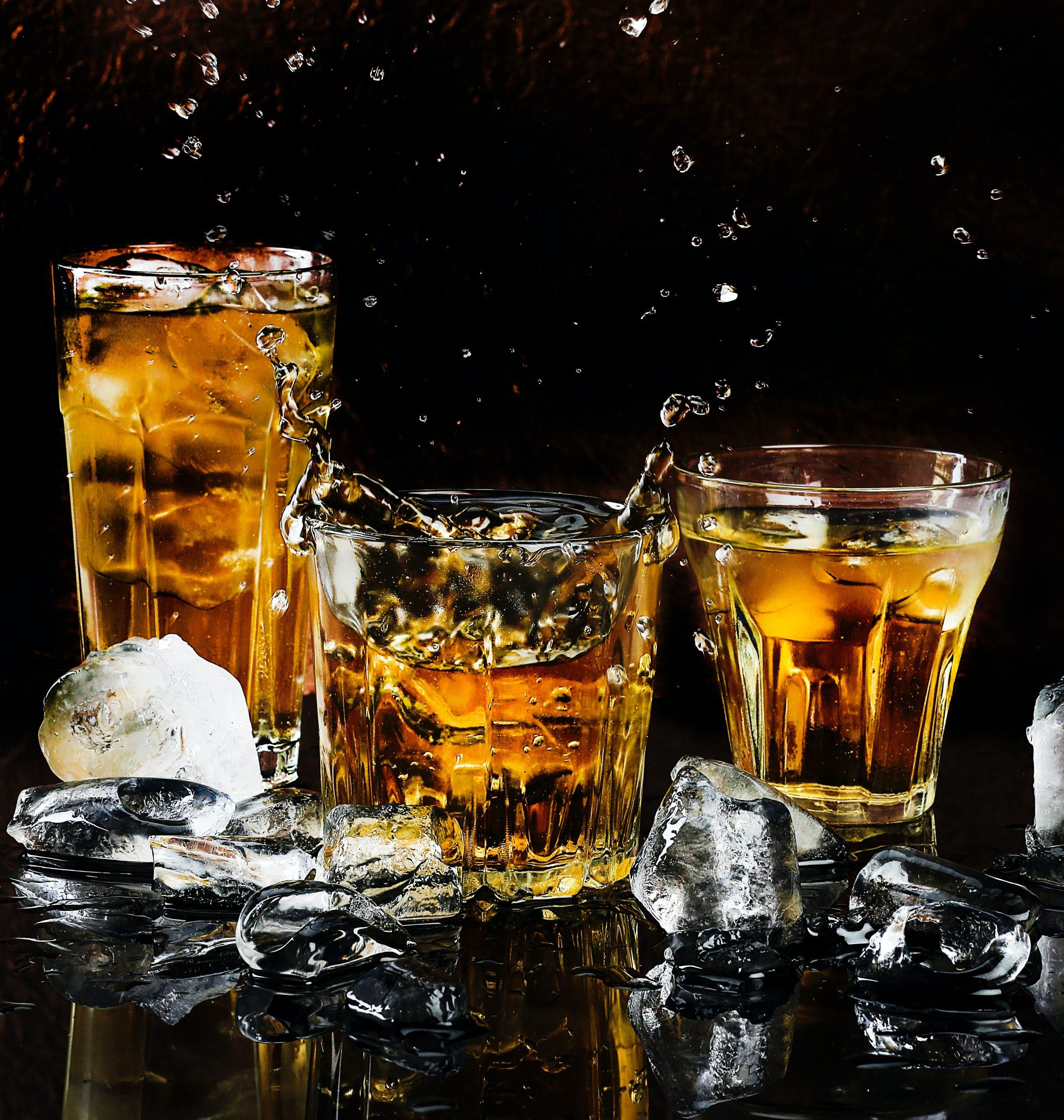 Imagem mostra um copo preenchido com bebida e pedras de gelo