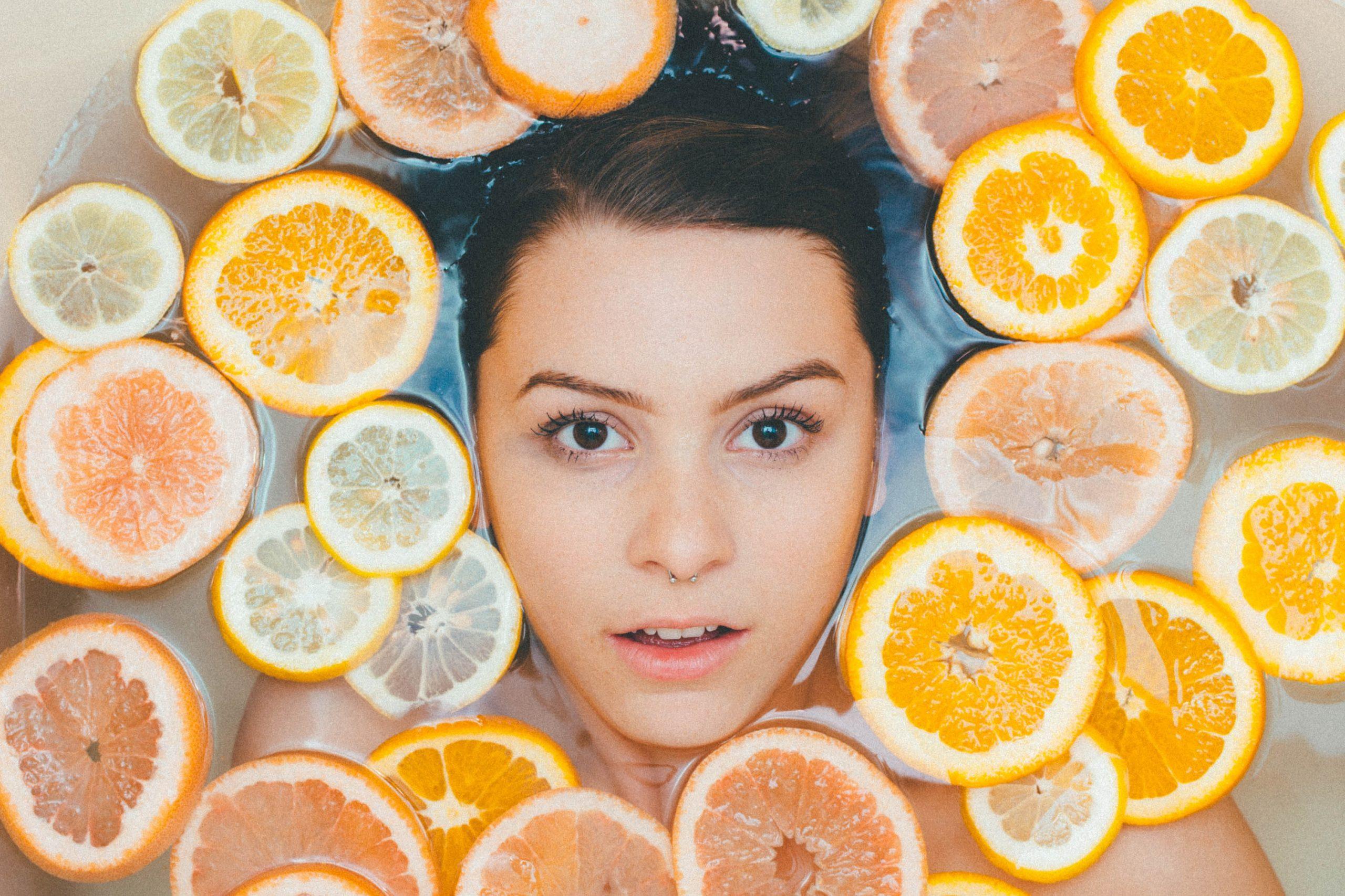 Imagem de uma mulher em uma banheira com rodelas de laranja.