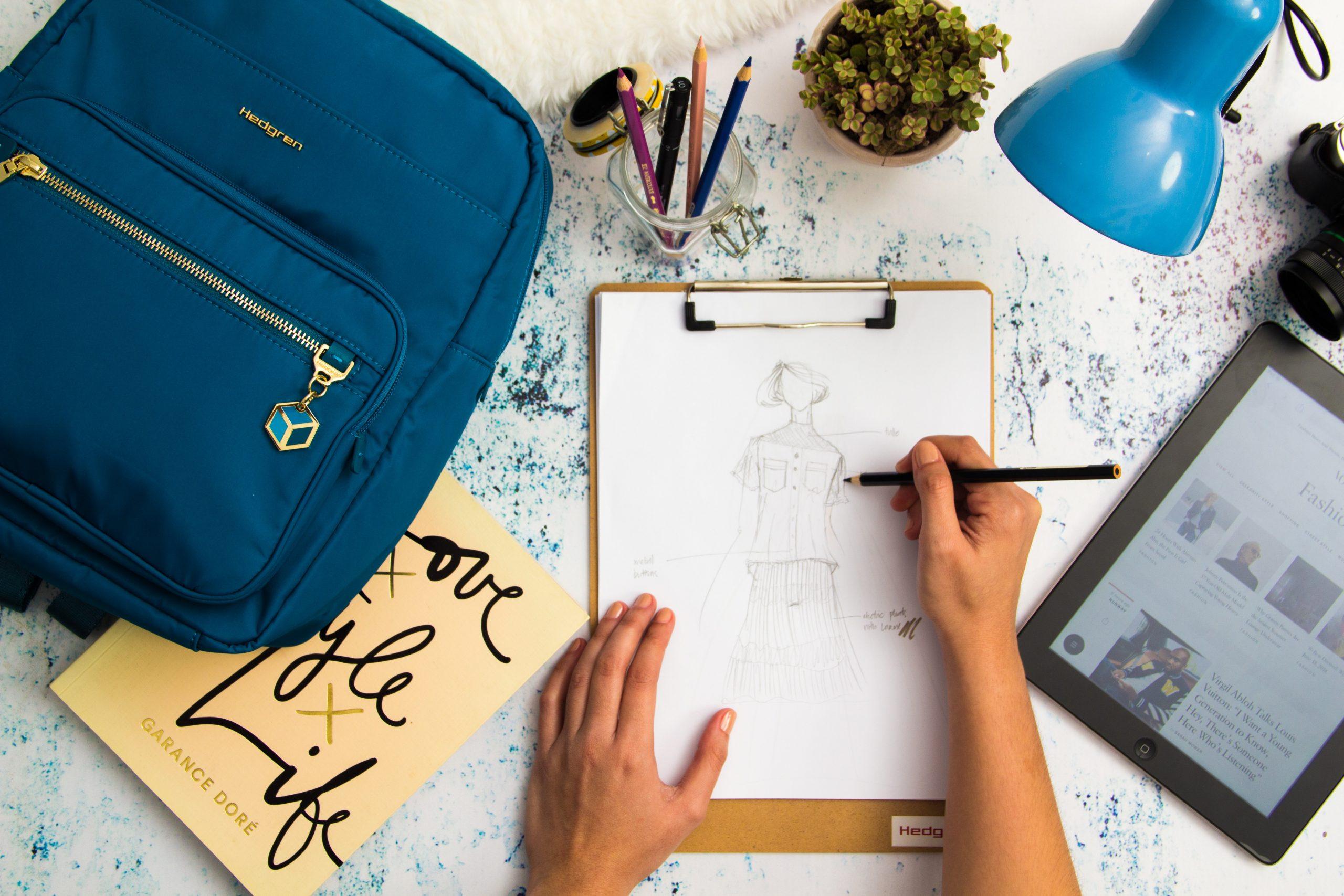 essoa desenhando em uma prancheta com mochila e tablet ao redor.