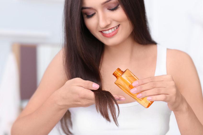 Imagem de uma mulher aplicando um reparador de pontas.