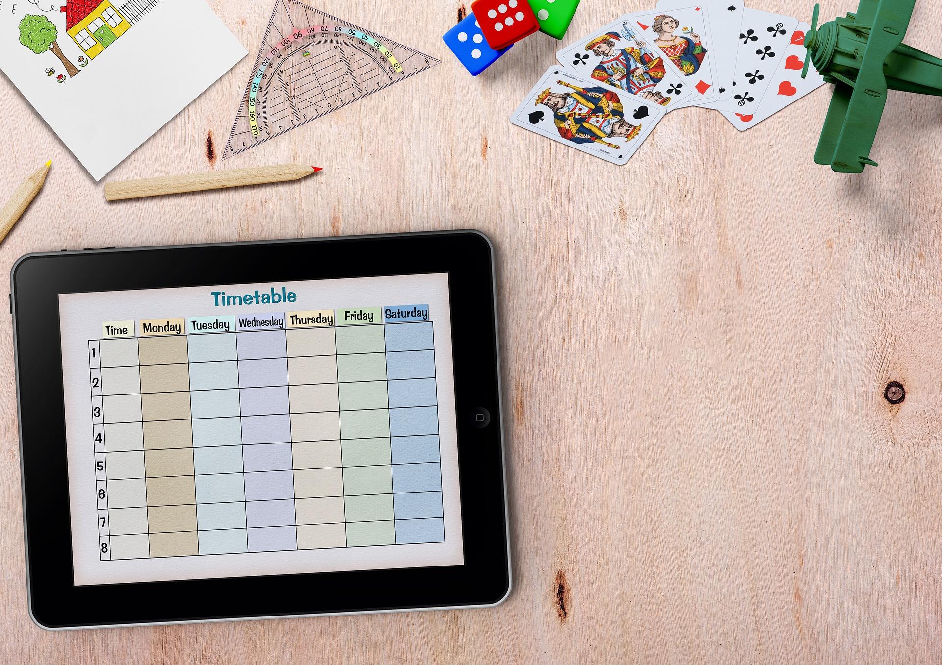 Tablet com calendário, compasso, cartas de baralho, lápis e desenhos ao redor.