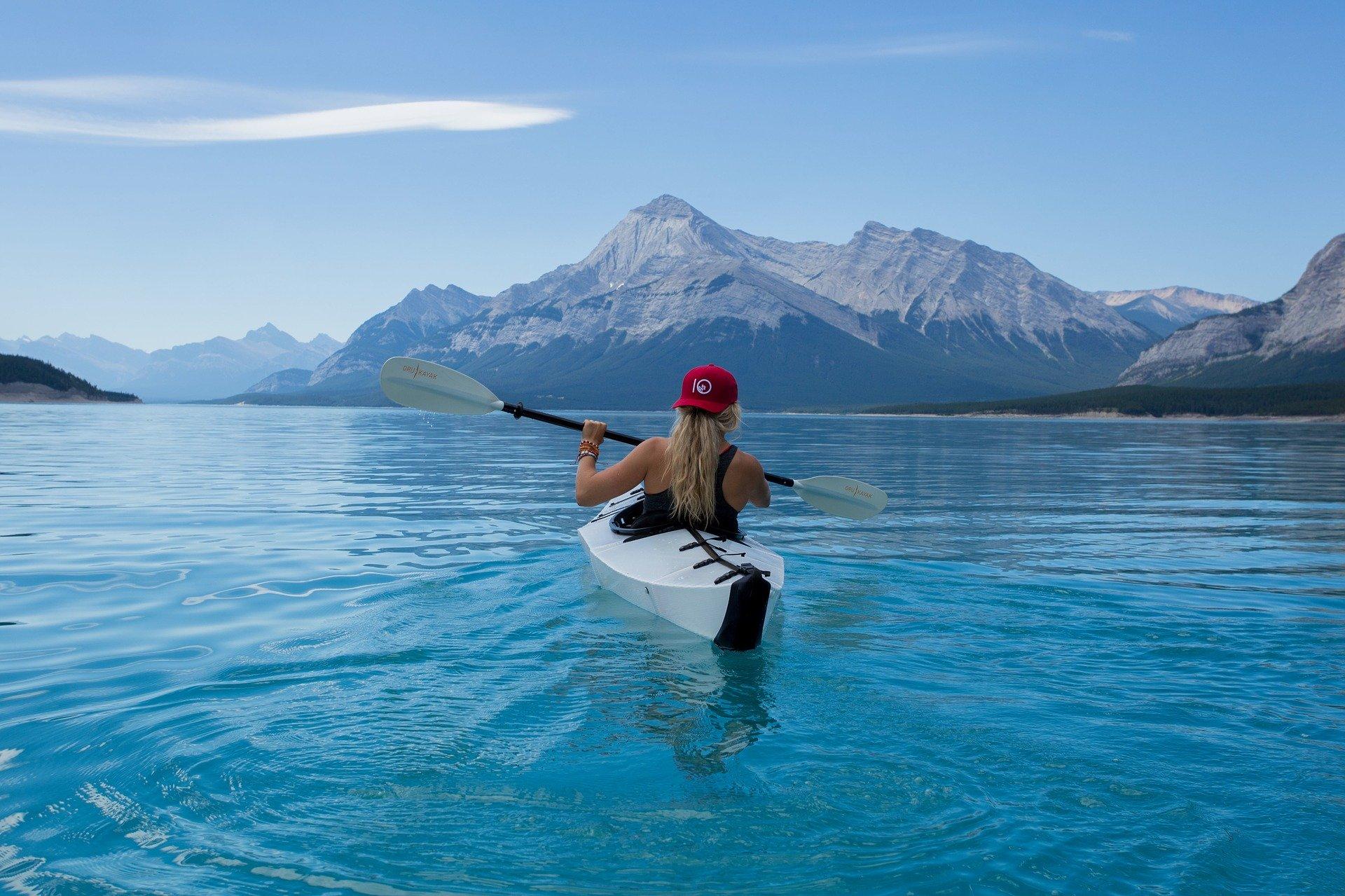 Foto de uma mulher loira em um caiaque, em um mar azul, com montanhas ao fundo.