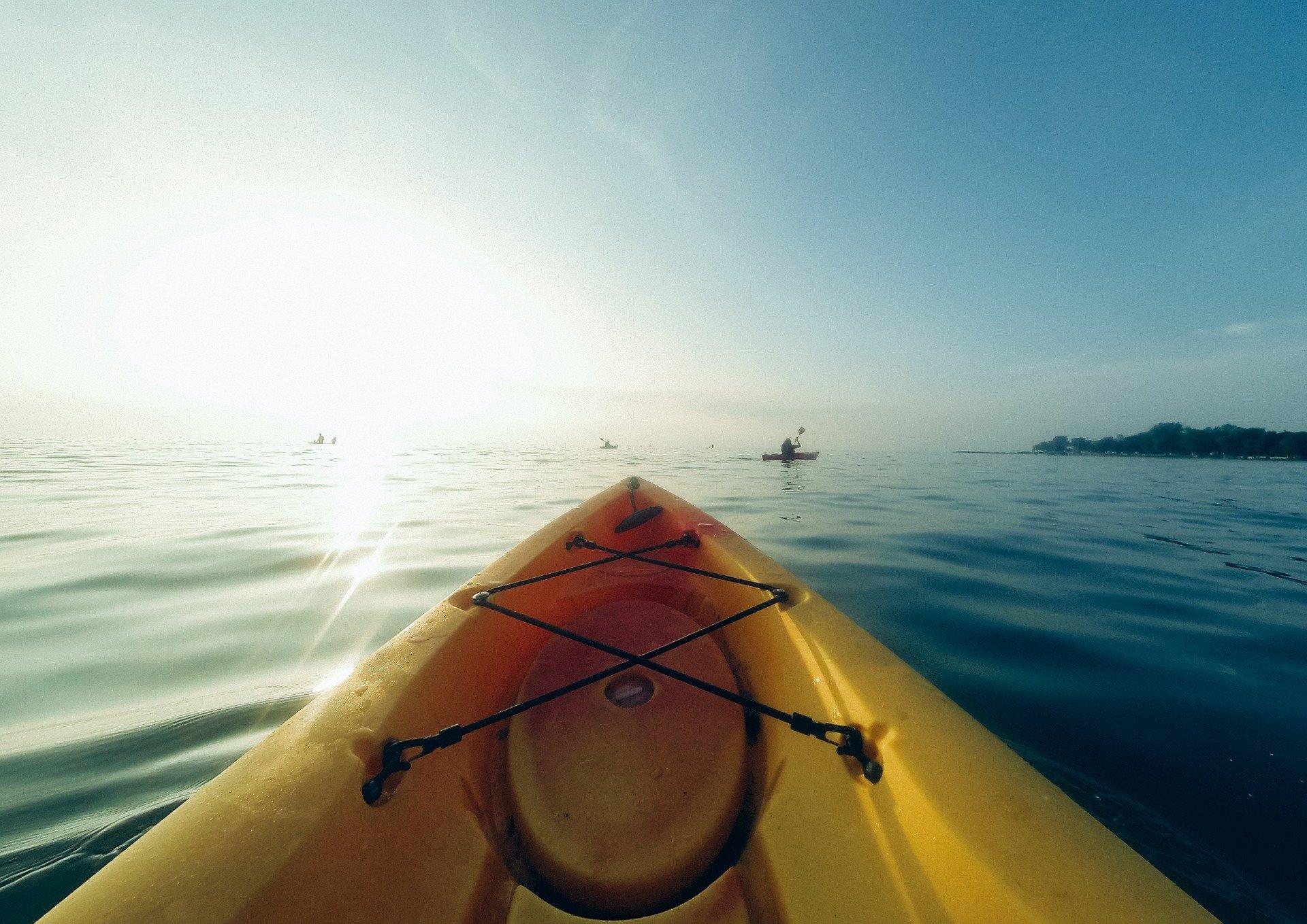 Imagem mostra o bico de um caiaque amarelo no mar, com o sol forte ao fundo, e o céu azul.