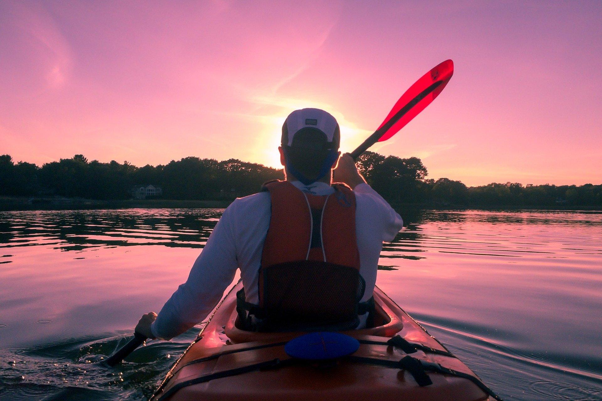 Imagem de um homem em um caiaque sit inside, de costas, em um rio, com por do sol ao fundo.