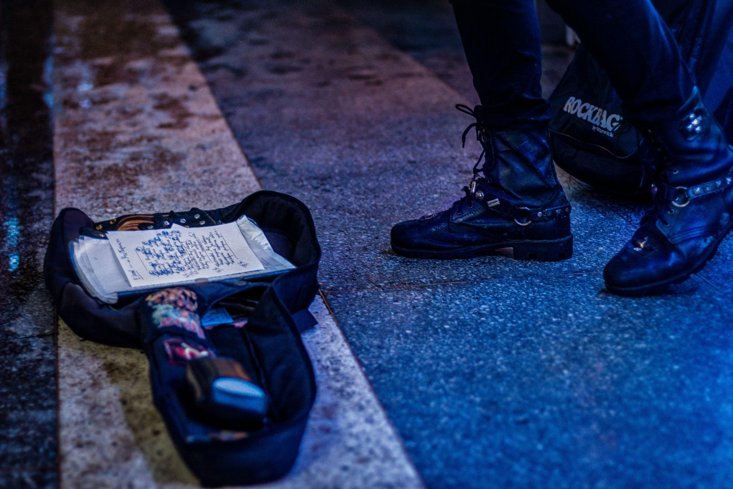 Imagem mostra as pernas de uma pessoa de coturno ao lado de uma bolsa aberta.