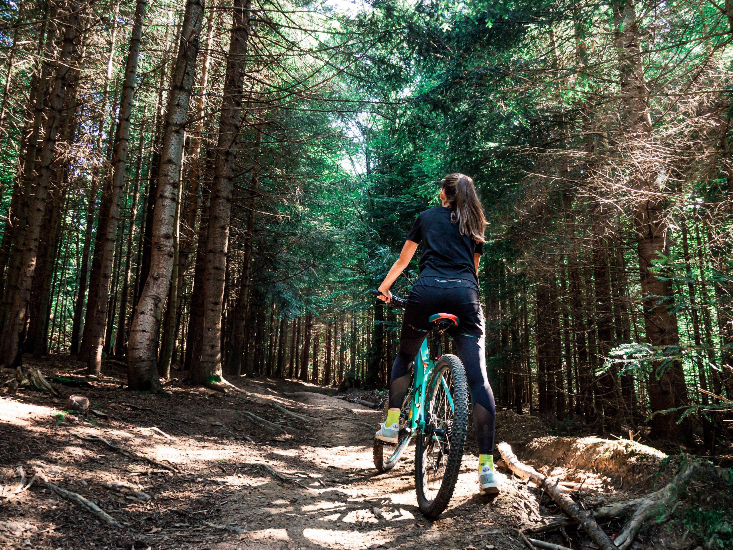 Imagem de uma mulher fazendo trilha de bicicleta.