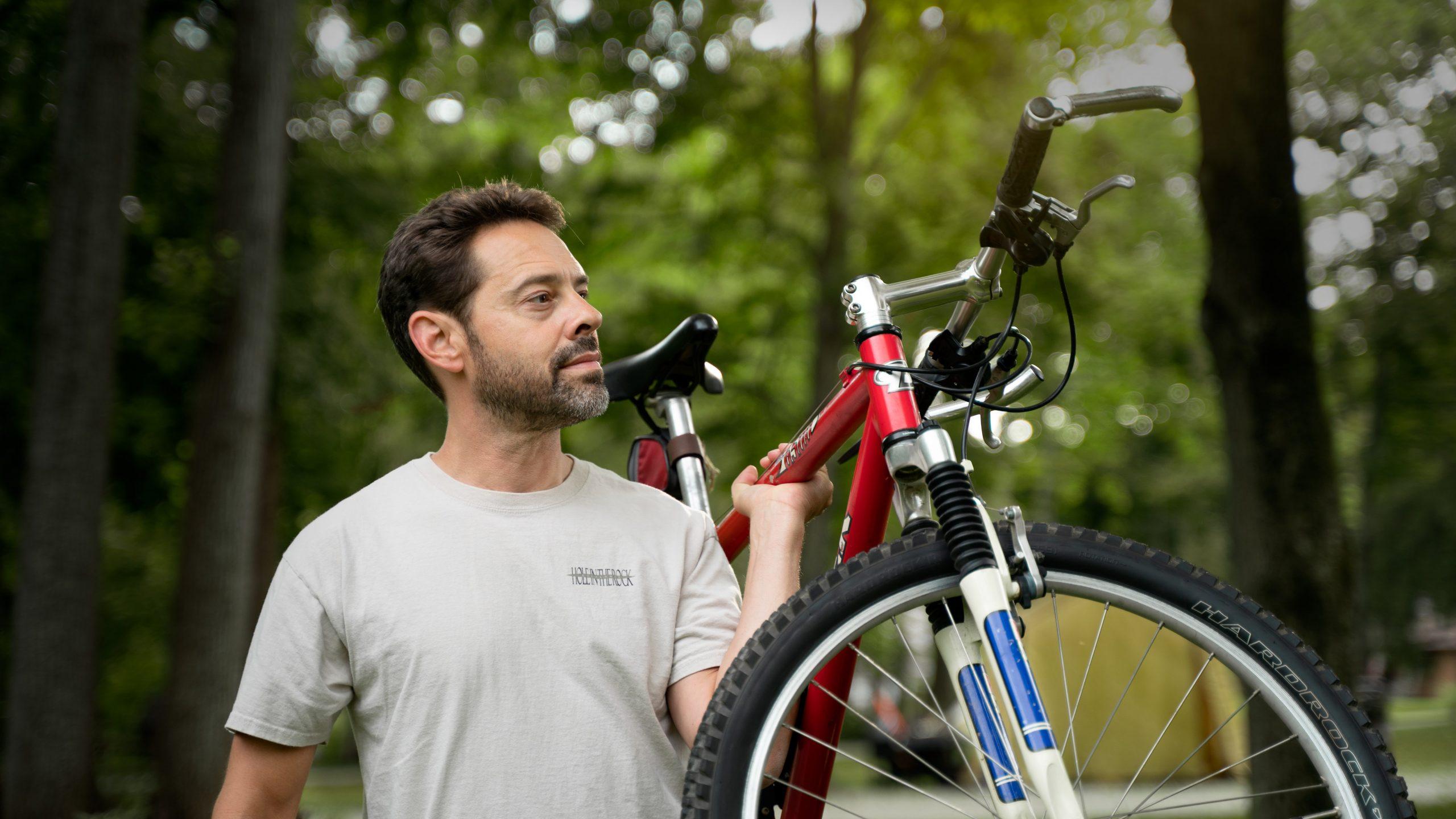 Imagem de um homem segurando uma bicicleta.