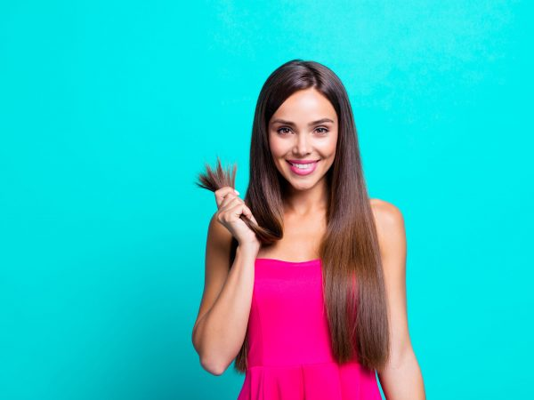 There is no problem! Cutting hair is unnecessary! Close up photo portrait of glad nice pretty satisfied lady holding in hand showing healthy ends isolated on bright blue background