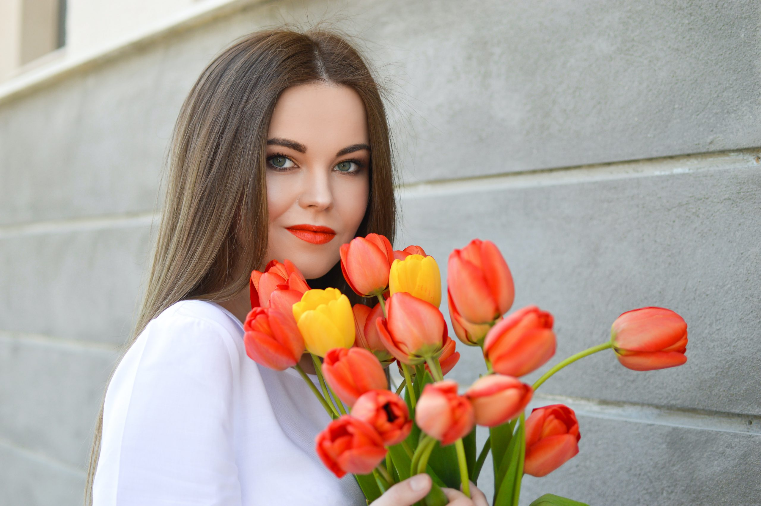 Imagem de uma mulher segurando um buquê de flores.
