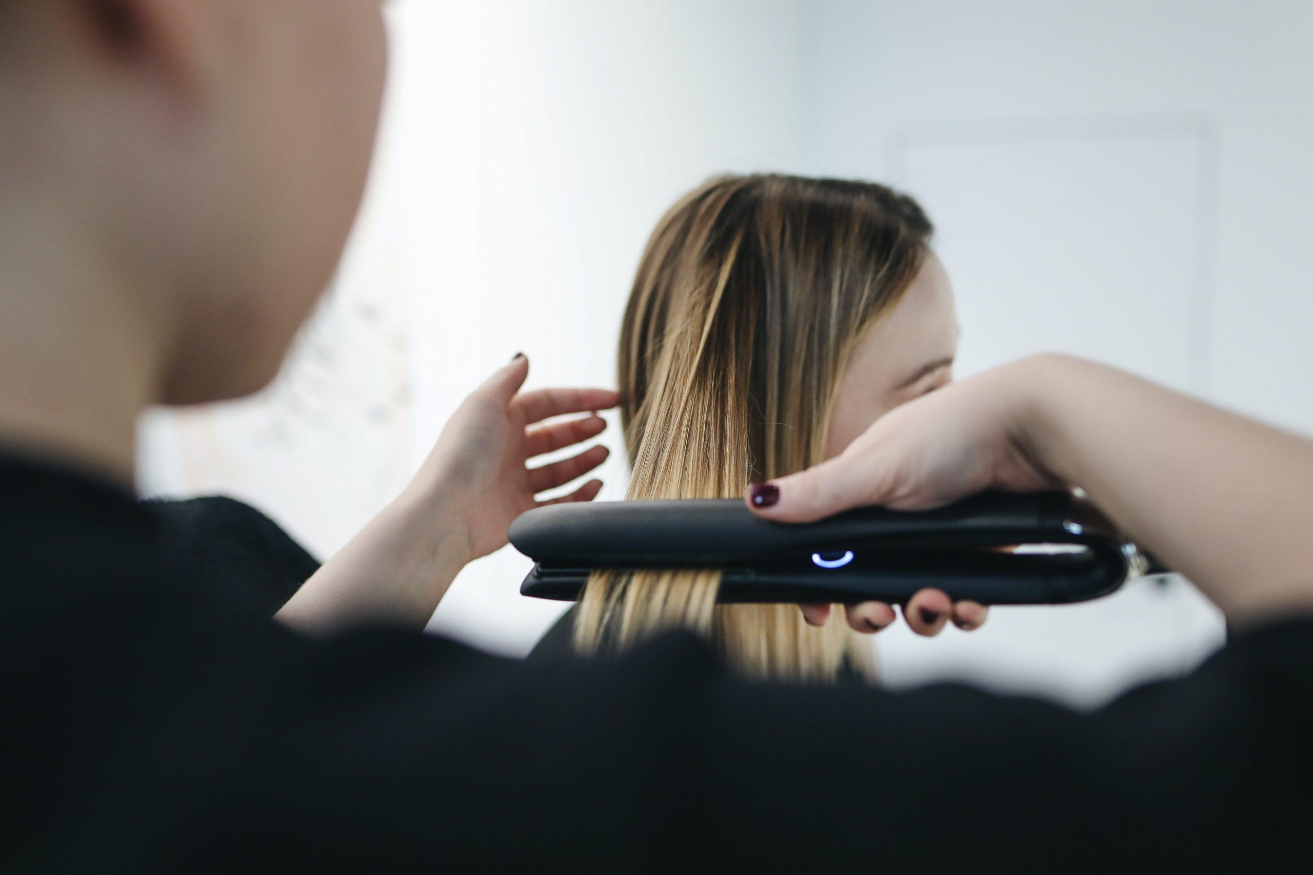 Imagem de um cabeleireiro alisando o cabelo de uma cliente.