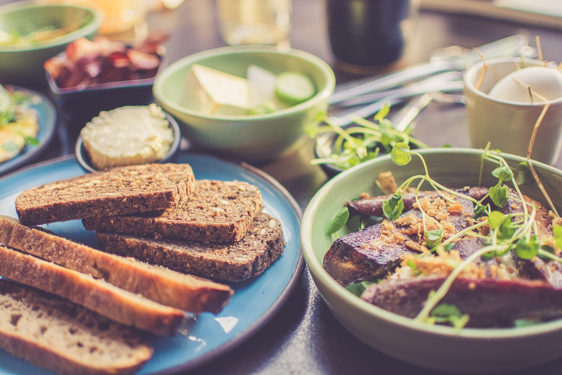 Mesa com vários pratos, incluindo pão integral e carne.