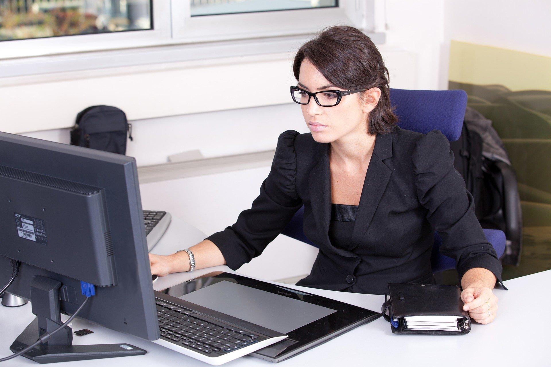 Imagem mostra uma mulher vestida de maneira formal em sentada em frente a um computador.