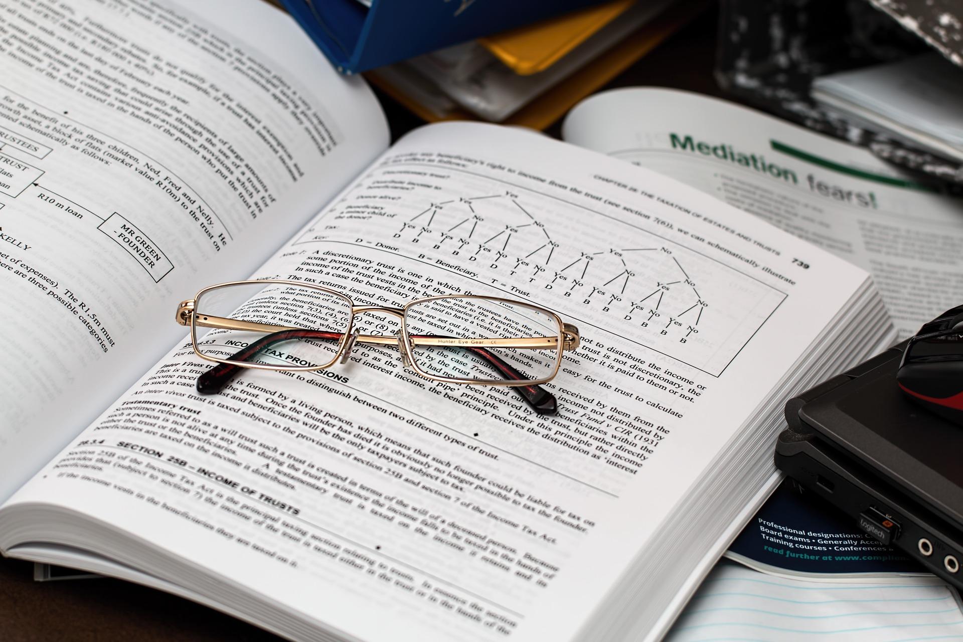 Imagem mostra um livro de contabilidade aberto sobre uma mesa.