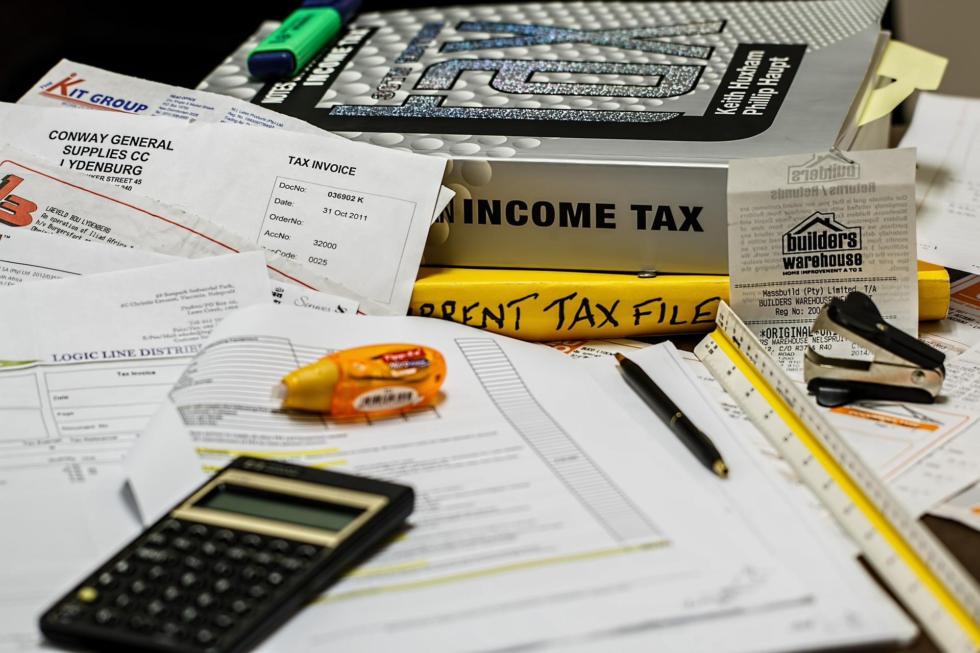 Imagem mostra uma mesa com diversos papeis e livros de contabilidade.