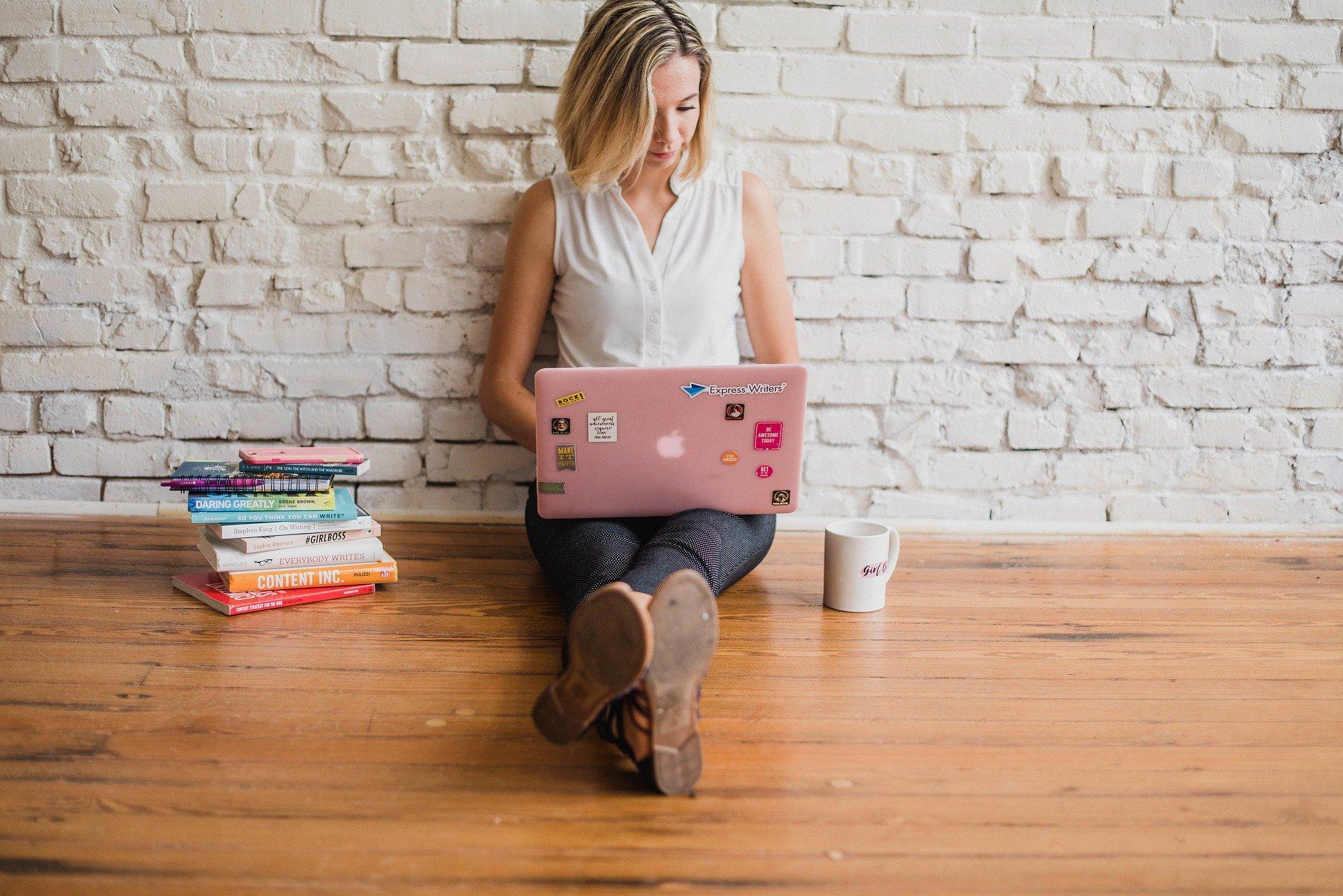 Imagem mostra uma mulher com um notebook ao lado de uma pilha de livros.