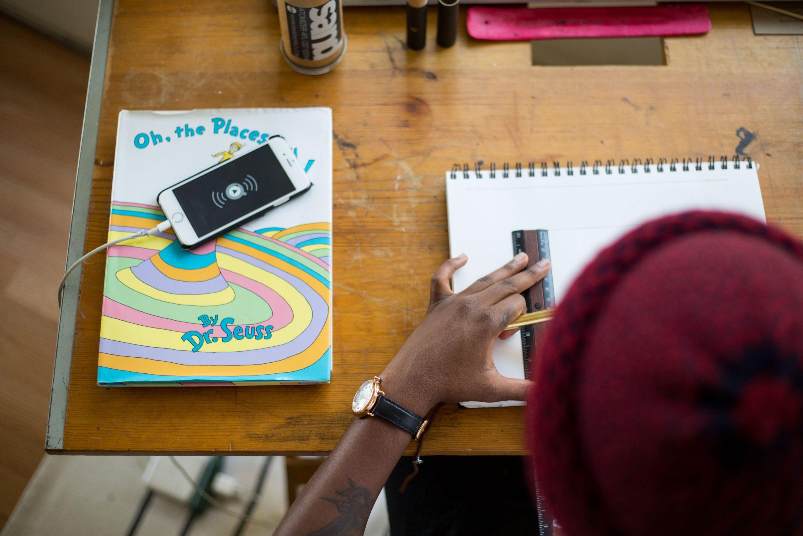 Na foto uma pessoa sentada escrevendo em um caderno com o celular carregando ao lado.