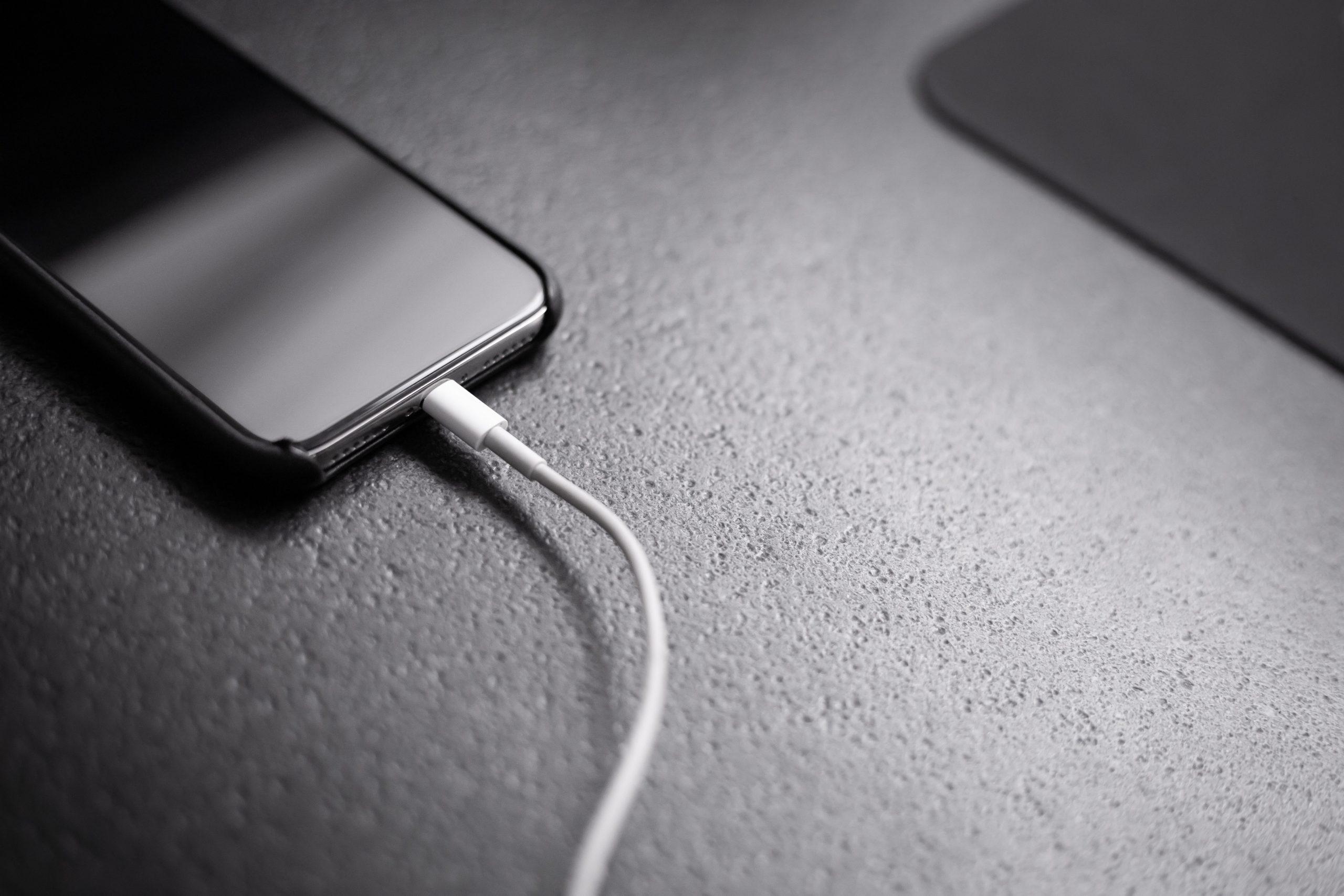 Na foto um iPhone conectado a um cabo de carregador.