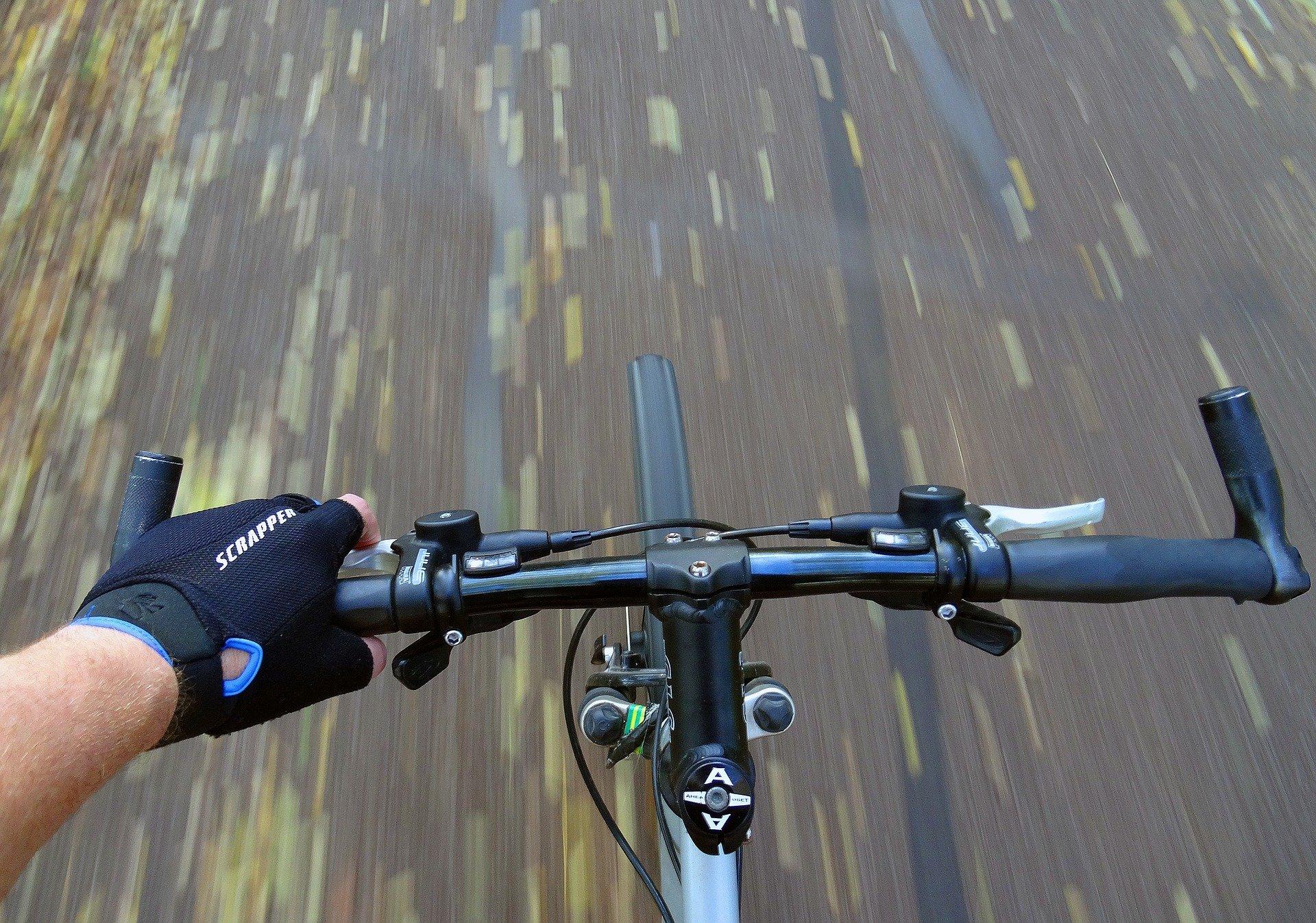 Imagem mostra uma pessoa pedalando uma bicicleta com bar ends.