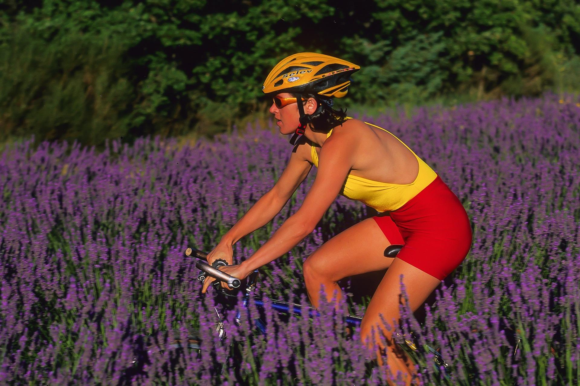 Imagem mostra uma mulher pedalando em um campo com flores.