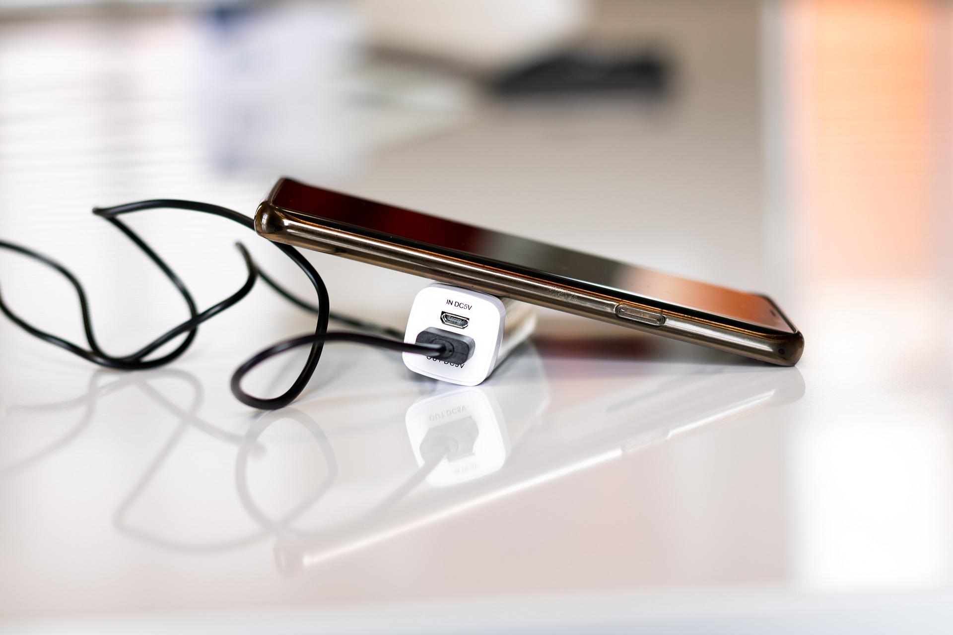 Na foto um celular em cima de um carregador portátil.