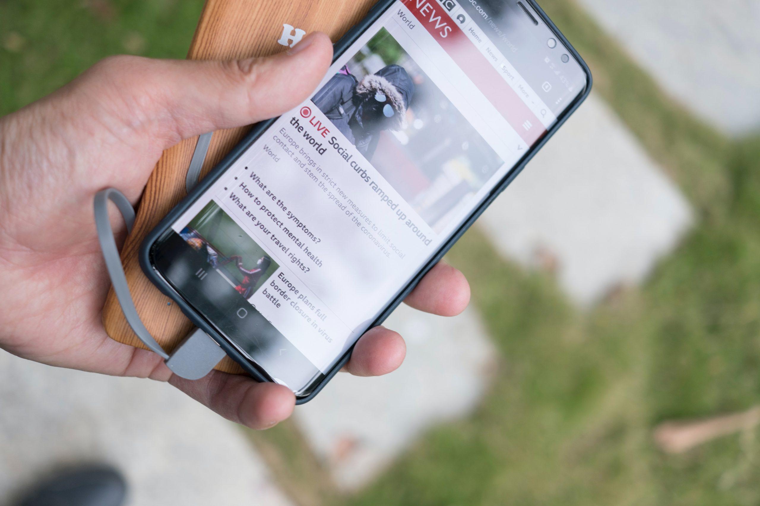 Na foto uma mão de homem segurando um celular e um carregador portátil.