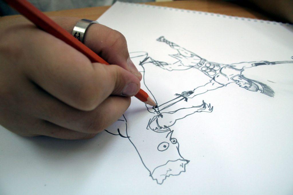 Imagem em preto e branco de uma pessoa sentada desenhando
